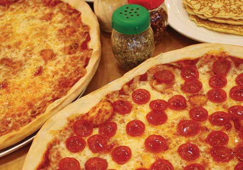 pepperoni pizza and cheese pizza on table with side of pancakes