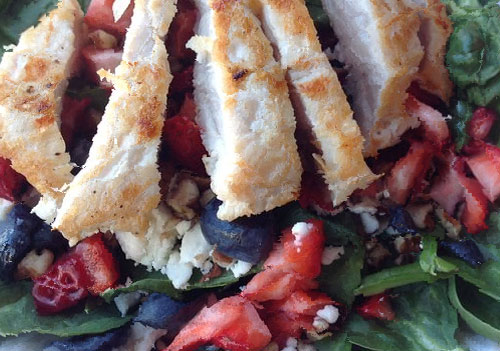 chicken on top of salad with berries and cheese crumbles