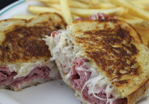 reuben sandwich on plate with fries